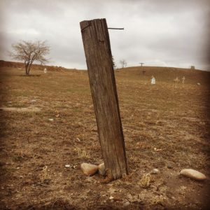 A lone wooden post with a single nail protruding from it. Who lies here and from when? No one will ever know.